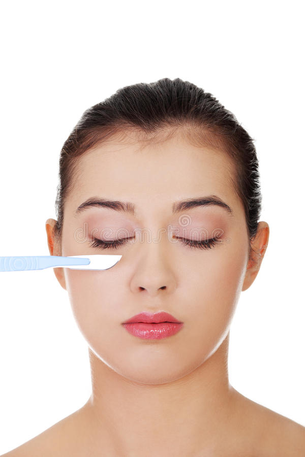 Download Female Face In Background Of Scalpel. Stock Photo - Image: 27267300