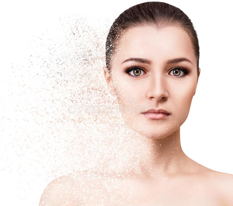 Female face crumbles into small particles. royalty free stock photography
