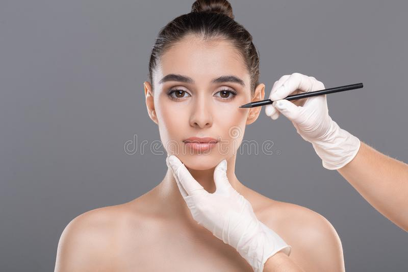 Female face with doctor`s hands with pencil. Beautiful woman ready for cosmetic surgery, female face with doctor`s hands with pencil stock image