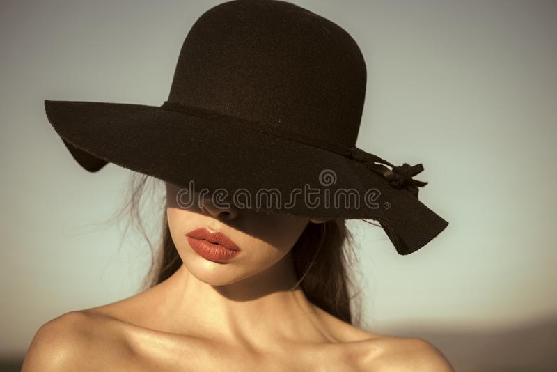 Female Face. Issues affecting girls. Portrait of elegant beautiful woman in a black wide hat on blue sky background. Female Face. Issues affecting girls royalty free stock photos