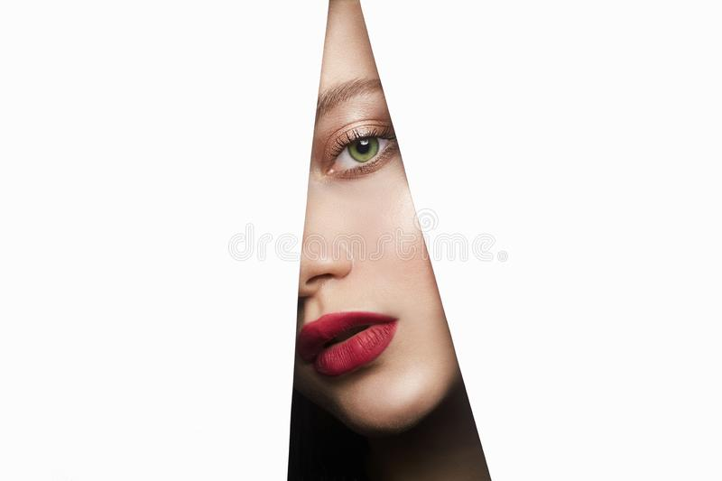 Female face with makeup into paper hole. make-up. Young beautiful woman. female face with makeup into paper hole. make-up artist concept. arrows on the eyes royalty free stock photo