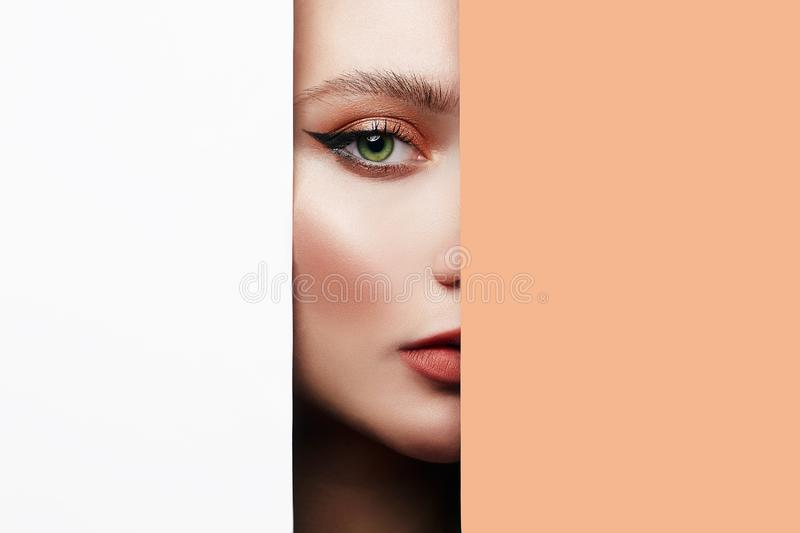 Female face with makeup into paper hole. Young beautiful woman. female face with makeup into paper hole. make-up artist concept. arrows on the eyes royalty free stock photography