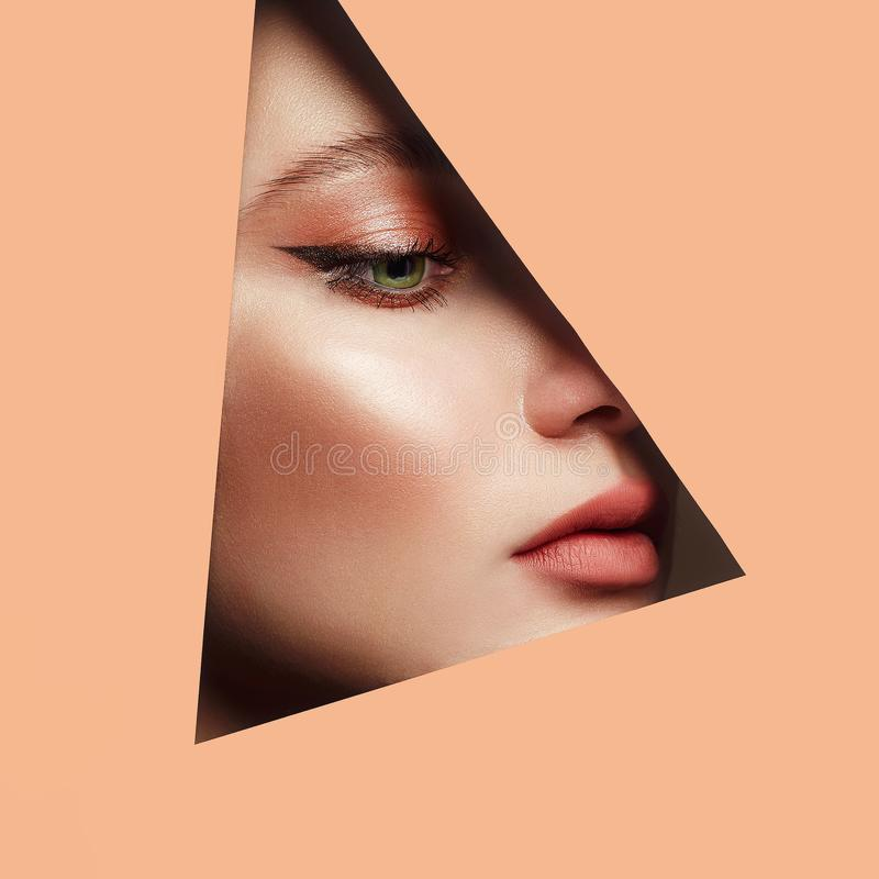 Female face with makeup into paper hole. Young beautiful woman. female face with makeup into paper hole. make-up artist concept. arrows on the eyes stock image