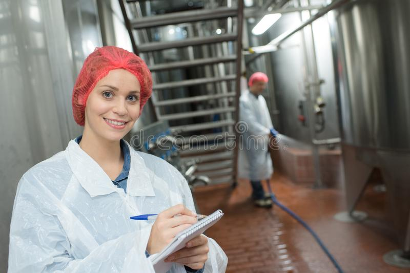 Female factory supervisor wearing hairnet and taking notes stock images