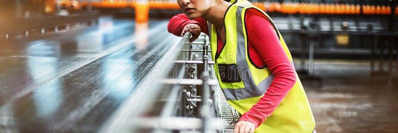 Female factory worker checking conveyor belt stock photos