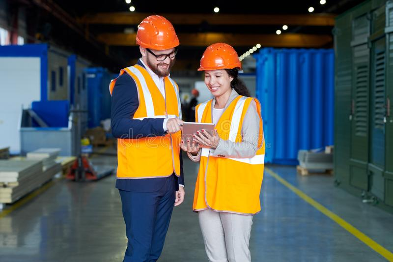 Female Factory Worker Talking to Investor. Portrait of female factory worker talking to businessman wearing hardhat while using digital tablet standing in stock image