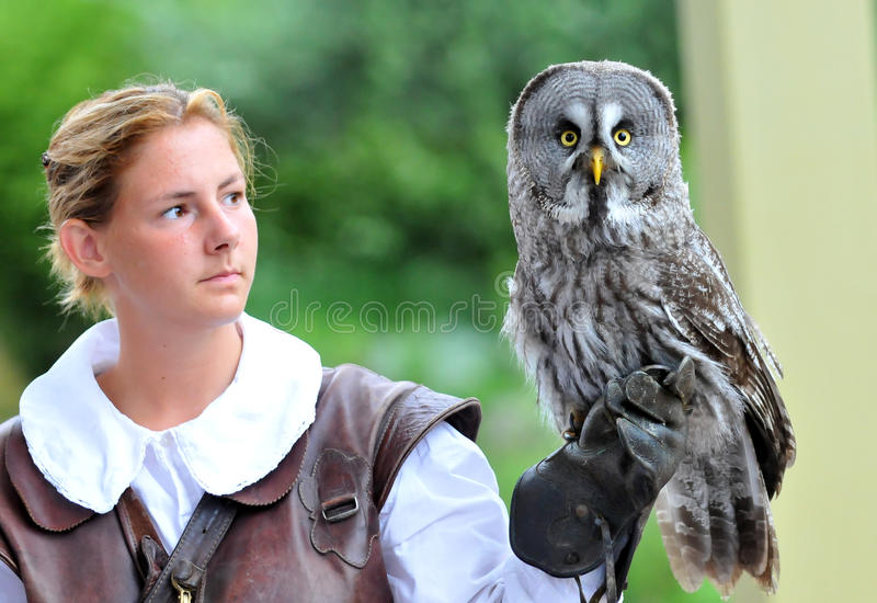 Female Falconer. LOCARNO, SWITZERLAND August 13: Female falconer holds a great grey owl at the Falconeria demonstration : August 13, 2010 in Locarno Switzerland royalty free stock photos