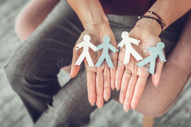 Female family therapist holding little models of couples in hands. Models of couples. Female family therapist holding little models of happy and unhappy couples royalty free stock images
