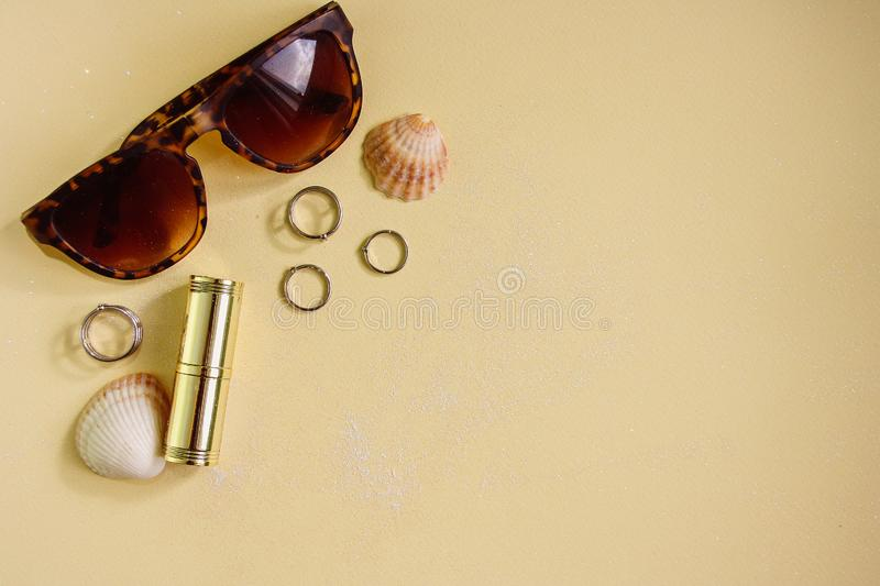 Female fashion accessories and shells on yellow pastel background. royalty free stock images