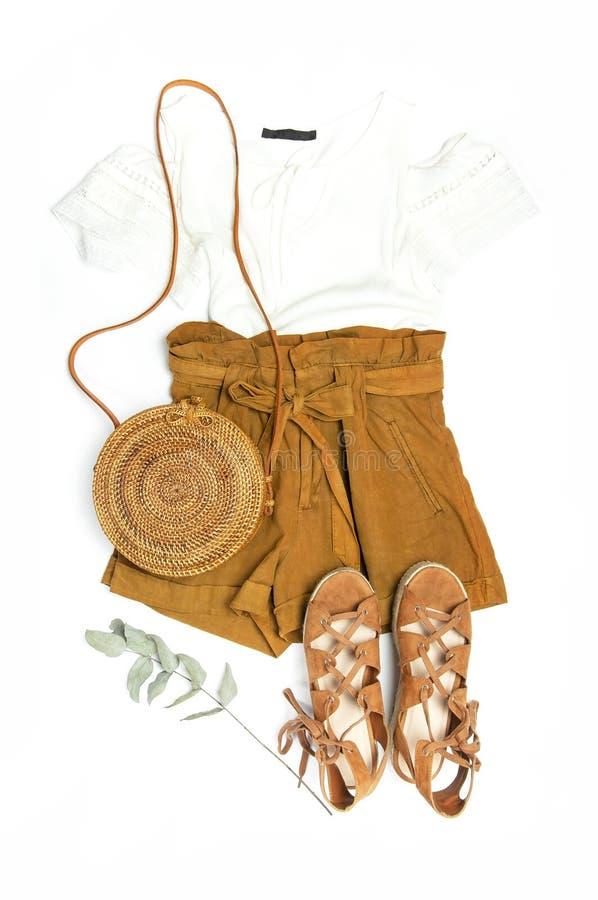 Female fashion background. Stylish trendy feminine summer clothing set. Shorts, white jacket, sandals, round rattan bag, sprig stock photo