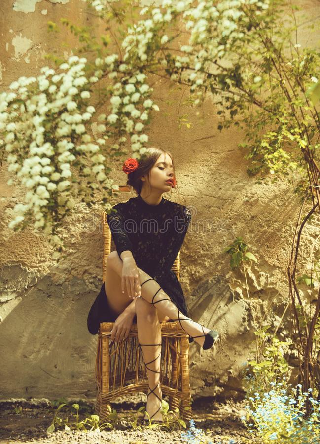 Female fashion, beauty and advertisement concept. Adorable woman sitting on wicker chair under blossoming flowers. Female fashion, beauty and advertisement royalty free stock photo
