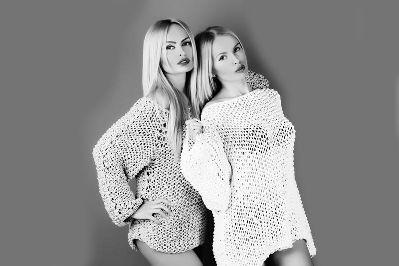 Female fashion and beauty. Two pretty girls with blond, long hair and sweaters stock photo