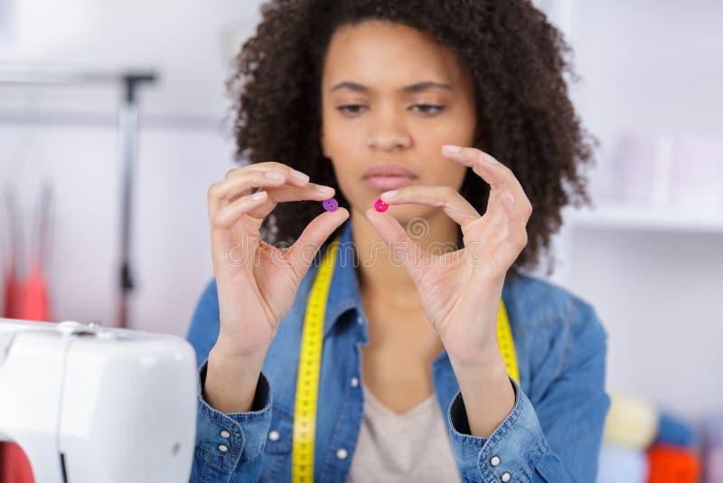 Female fashion designer choosing buttons stock photos