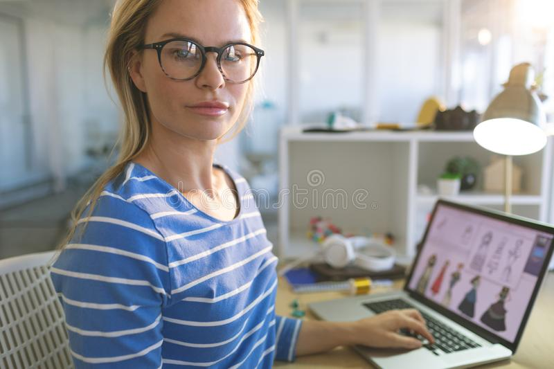 Female fashion designer looking at camera while working at desk. Portrait of young Caucasian blonde female fashion designer looking at camera while working at royalty free stock photography