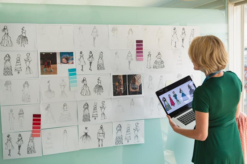 Female fashion designer looking at sketch while holding laptop in design studio. Rear view of beautiful mature Caucasian female fashion designer looking at royalty free stock photos