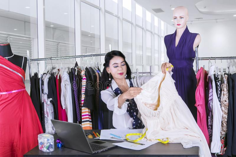 Female fashion designer measure fabric in workplace stock photography