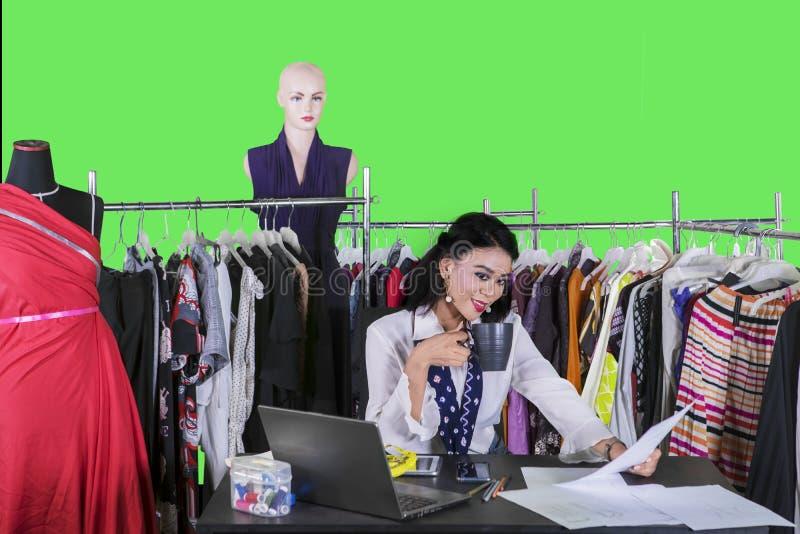 Female fashion designer relaxing on studio royalty free stock photo