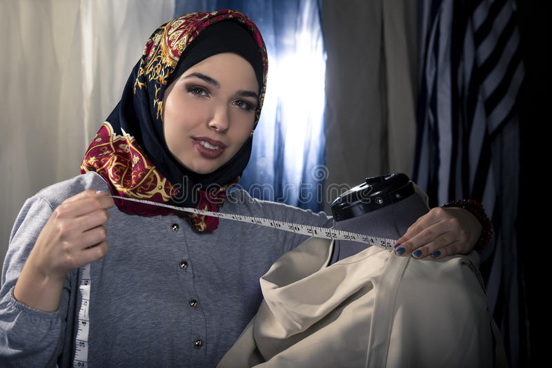 Female Fashion Designer Wearing Hijab. Female fashion designer tailoring conservative clothing in a textile workshop. The hijab she is wearing is associated with royalty free stock photos
