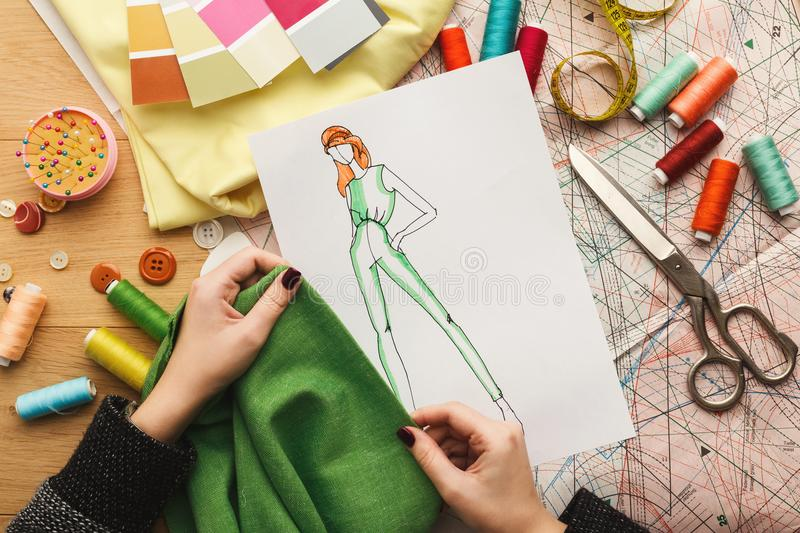 Female fashion designer working with fabric sample and drawn illustration stock images