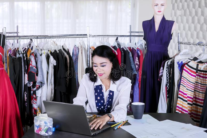 Female fashion designer works with a laptop royalty free stock photo