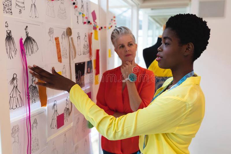Female fashion designers discussing over sketch design. Side view of diverse female fashion designers discussing over sketch design in design studio. This is a royalty free stock photo
