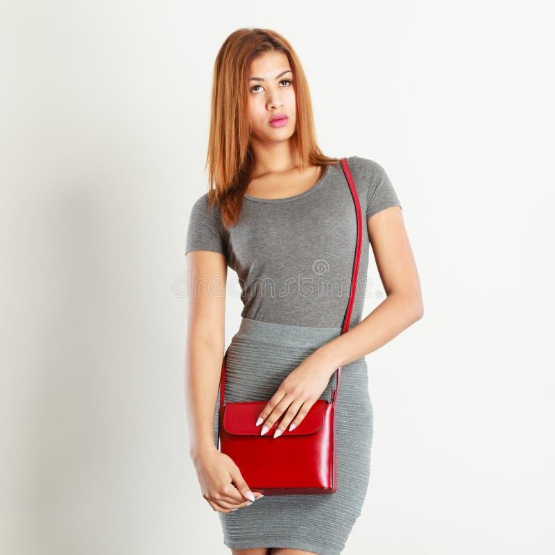 Mulatto girl gray wear with red handbag stock photo