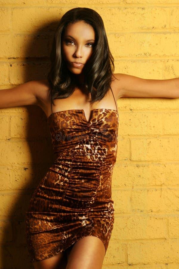 Female fashion model pose. Female fashion model posing in stylish dress against yellow brick wall royalty free stock image