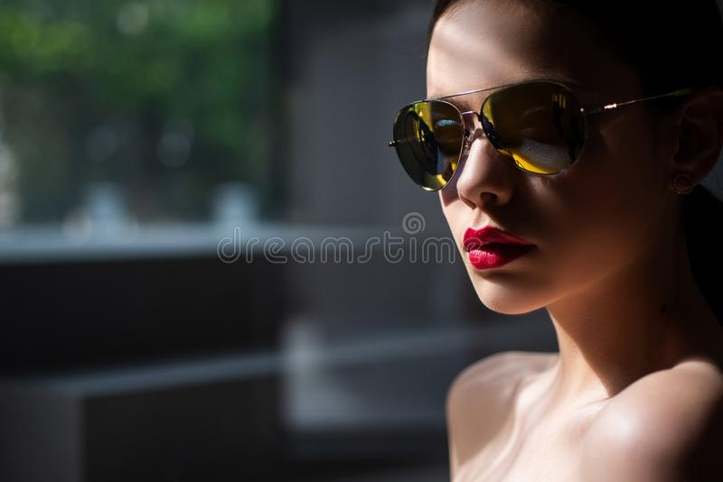 Female fashion model posing with sunglasses. Sexy. Close-up portrait of a beautiful charming young attractive woman in a stock photography