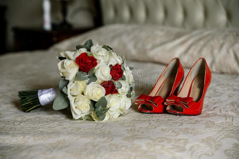 Female fashion red wedding shoes with bride`s bouquet of white and red roses lie on the bed. Close up stock photo