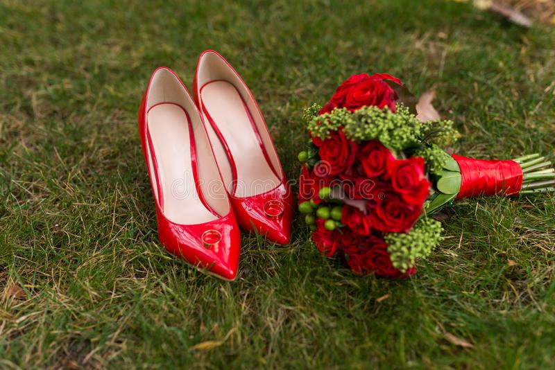Female fashion red wedding shoes with golden rings on them in focus and bride`s bouquet with red roses and green berries out of fo stock images