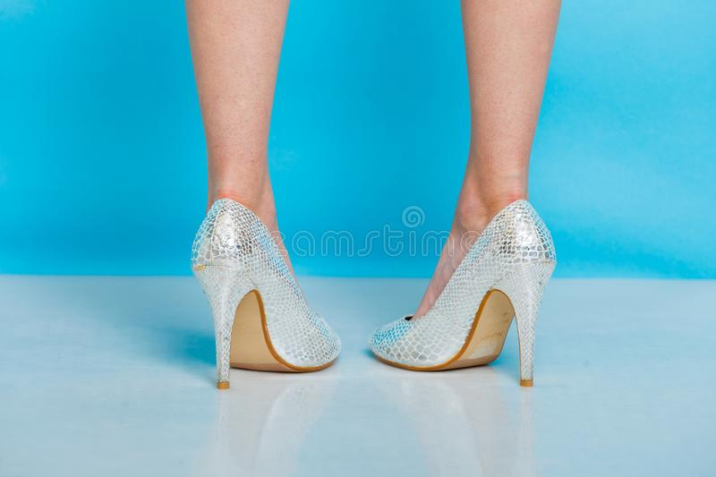 Female legs in silver high heels shoes stock photo