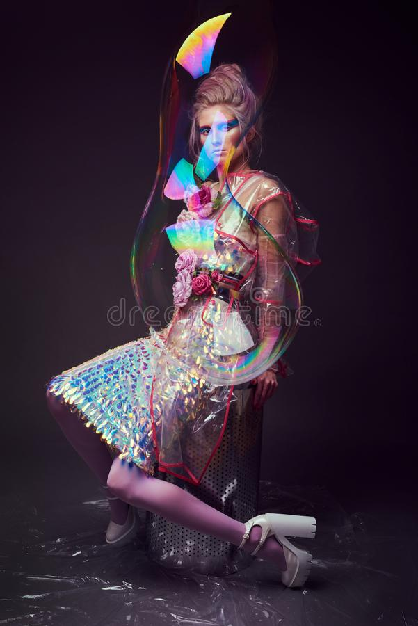 Female in fashion transparent raincoat with splendid make up and hairstyle royalty free stock image