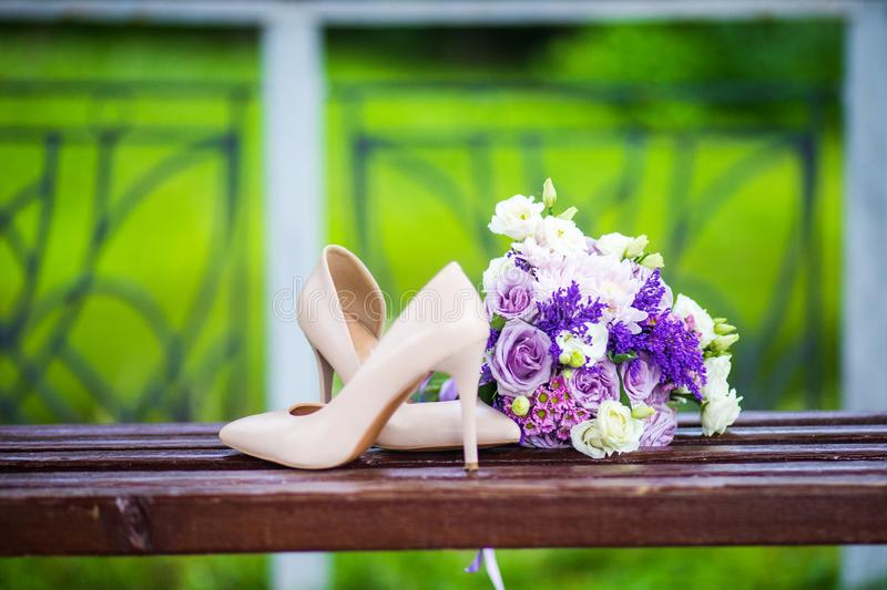 Wedding shoes with elegant bride`s bouquet. Female fashion wedding shoes with elegant bride`s bouquet in pastel tones on green grass background. Wedding details royalty free stock photography