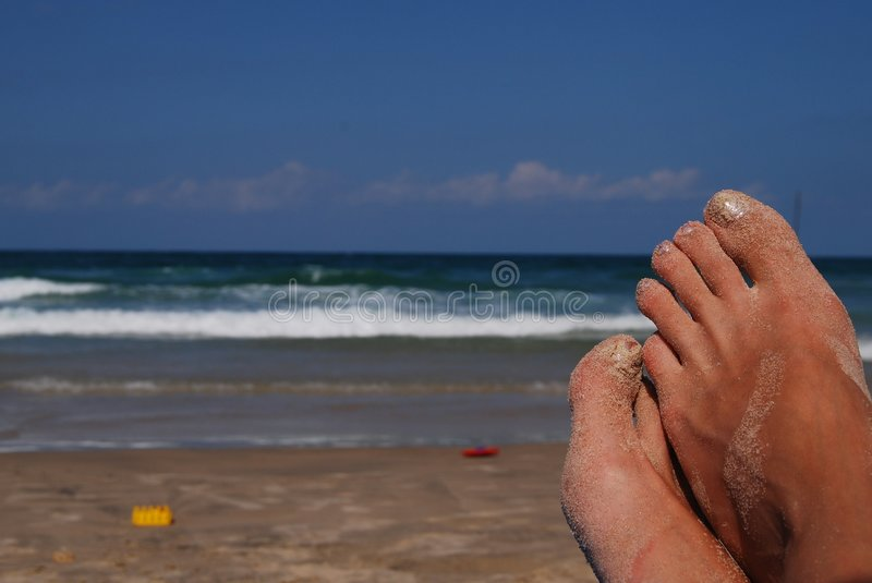 Female feet. On back-ground sea in sand royalty free stock image