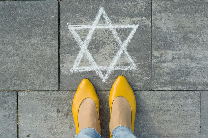 Female feet with abstract image of six pointed star, written on grey sidewalk stock photos