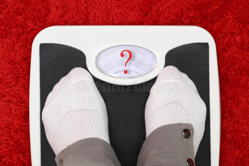 Female feet on bathroom scale stock photo