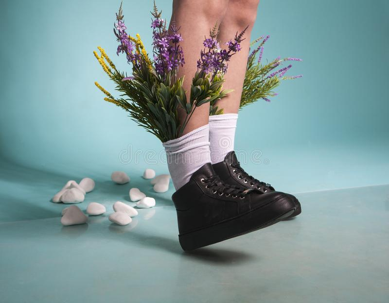 Female legs in black shoes and white socks with flowers stock photo