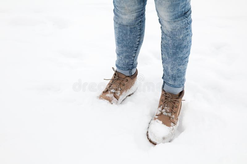 Female feet in blue jeans and high boots stock photography