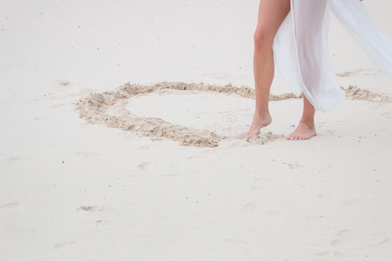 Female feet closeup of woman standing at the sandy beach next to the heart. she paints it.  royalty free stock photography