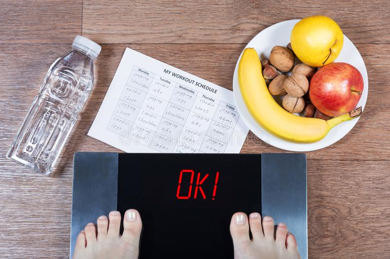 Female feet on digital scales with word ok surrounded by bottle of water, plate with healthy food and workout schedule paper. stock images