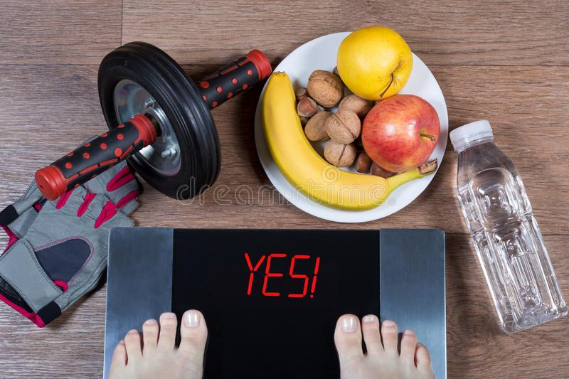 Female feet on digital scales with word yes surrounded by sport accessories AB roller wheel, fitness gloves, healthy food. stock image