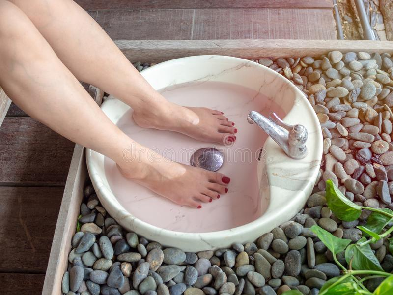 Female feet in foot spa marble basin. Epsom salt foot soak concept royalty free stock photo