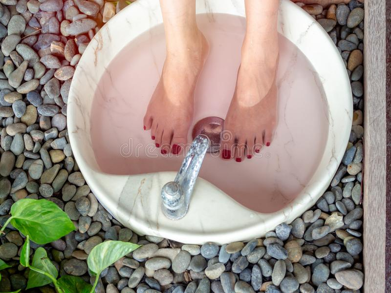 Female feet in foot spa marble basin. Top view. Epsom salt foot soak concept royalty free stock image