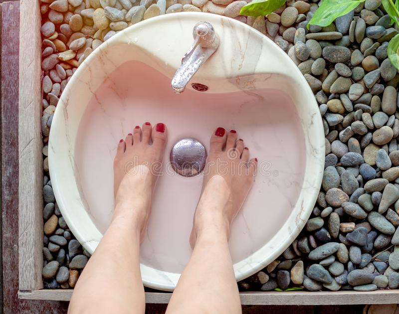 Female feet in foot spa marble basin. Top view. Epsom salt foot soak concept stock image