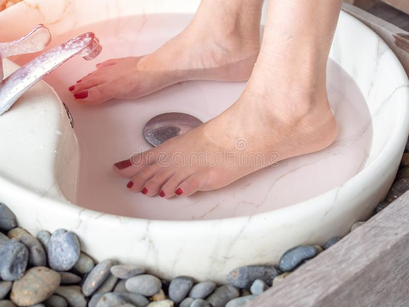 Female feet in foot spa marble basin. With water flowing from faucet. Epsom salt foot soak concept royalty free stock photography