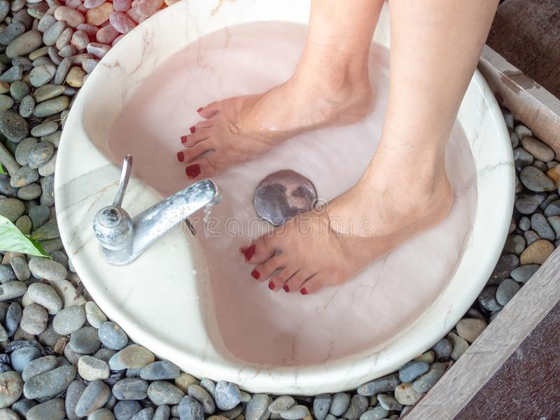 Female feet in foot spa marble basin. With water flowing from faucet. Epsom salt foot soak concept stock photos