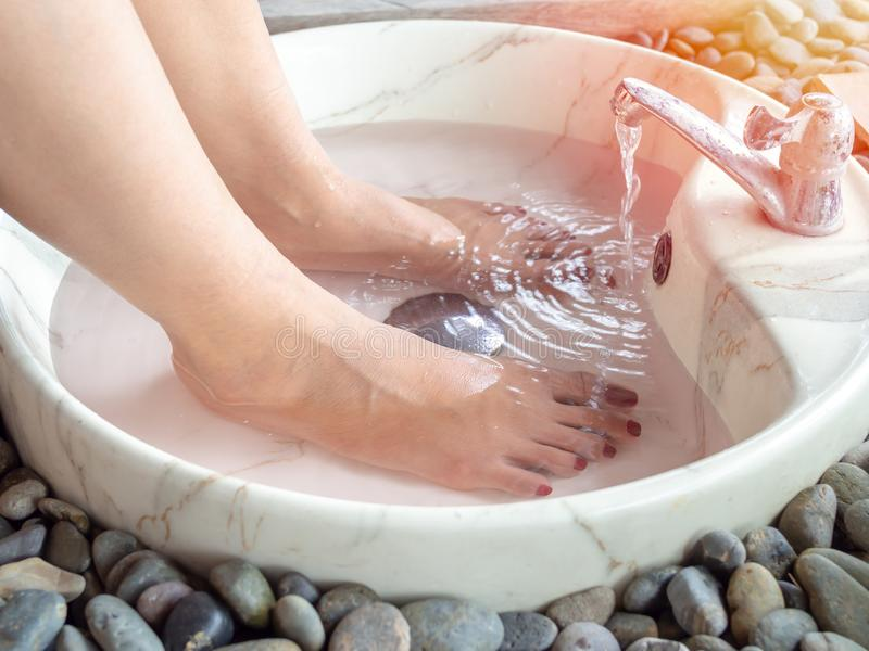 Female feet in foot spa marble basin with water flowing from faucet. Epsom salt foot soak concept stock photo