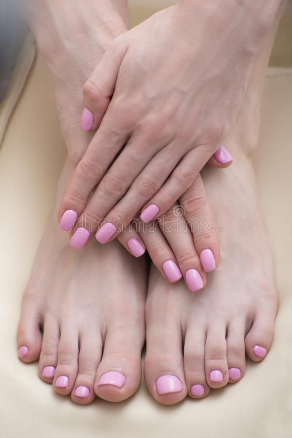 Female feet and hands with a pink manicure. Beauty saloon. Close-up.  royalty free stock photo