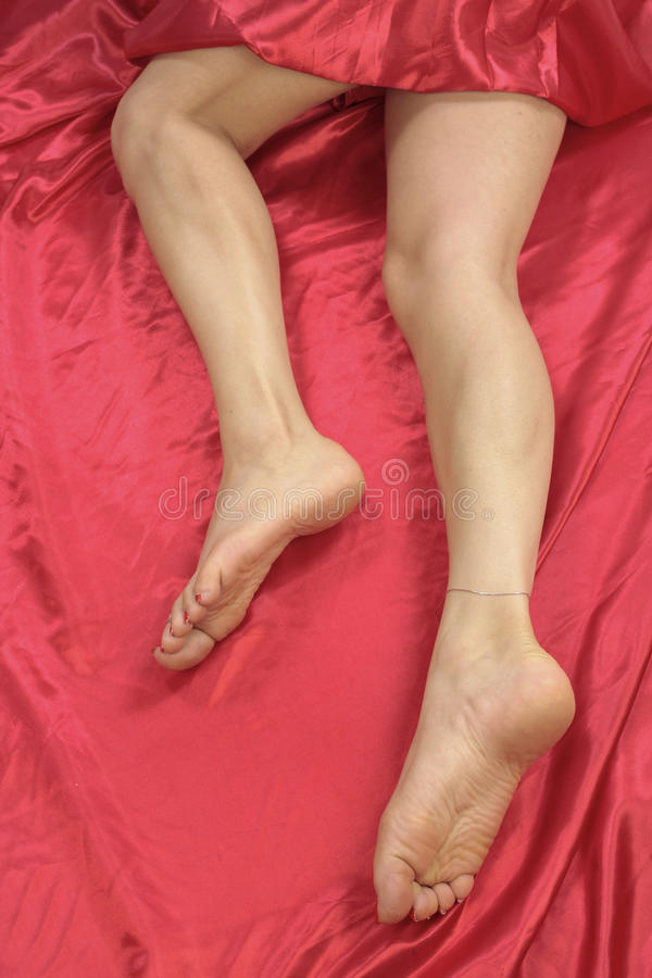 Female Feet And Legs Over Red Stock Photo