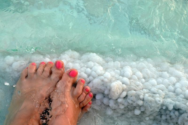 Female feet with manicure on stone, covered with salt formations between the waves in the water. Crystallization of salt on stone. Spa, therapy in the Dead Sea stock photo